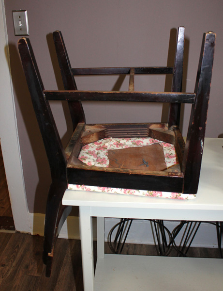 The chair upside down on a table to reattach the seat