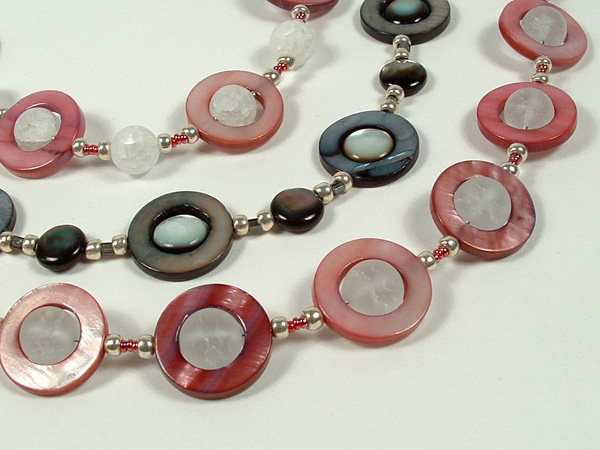 Close-up photo of the trio of UFO shell necklaces.