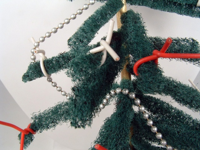 Close-up of ball-chain garland and red/white wire ornaments.