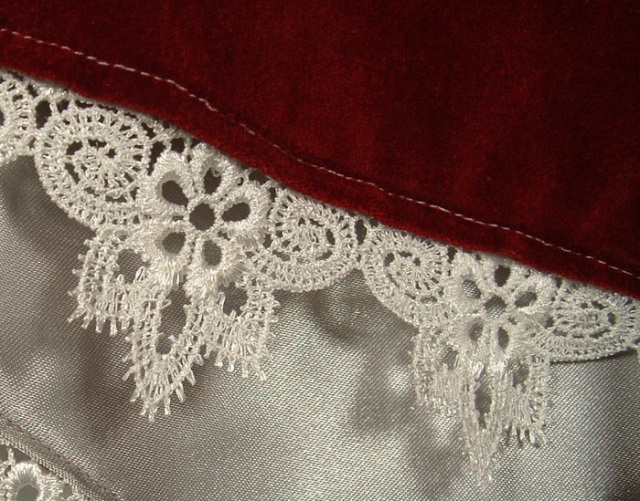 Close-up photo of lace on the velvet and brocade cape.