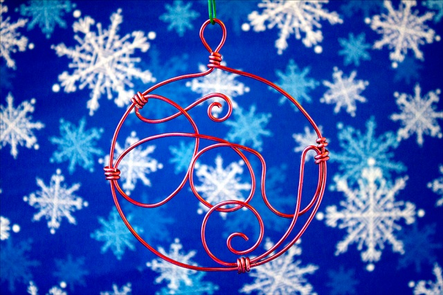 "Word ""Joy"" wire-wrapped inside wire circle."