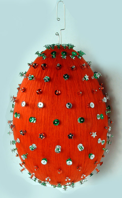 Red thread wrapped ornament with sequins and pins.