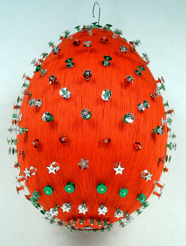 Bottom view of red thread wrapped ornament with sequins and pins.