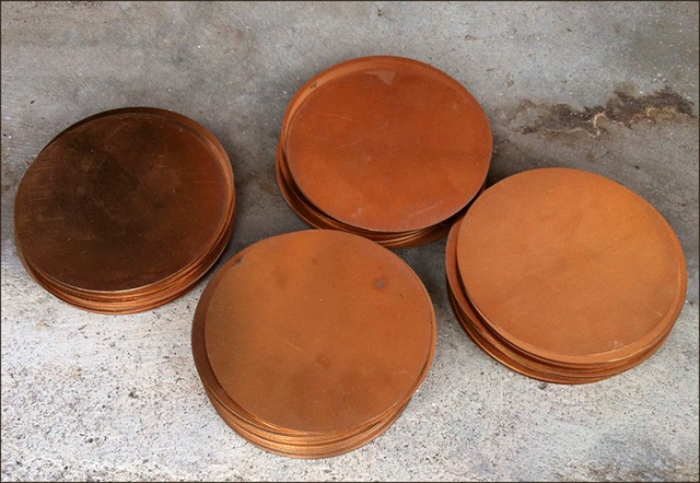 Photo of 4 stacks of copper discs.