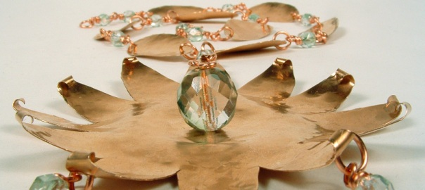 View of copper star-burst necklace from the bottom of the pendant.