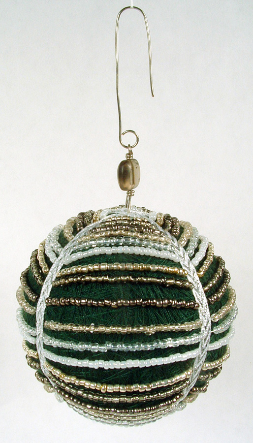 Green thread ball draped with stands of seed beads.