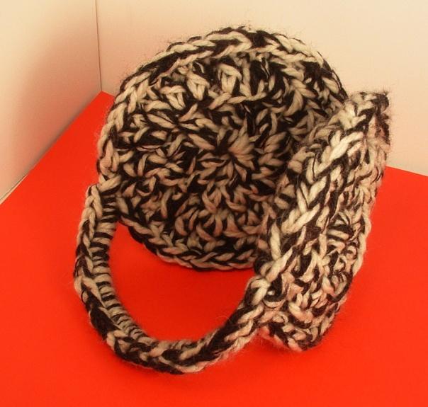 Crocheted earmuffs in cream and black wool yarn.