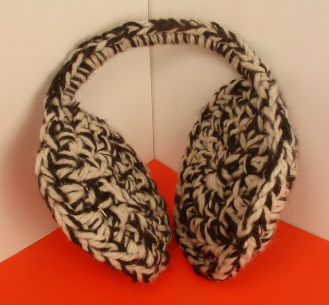 Crocheted earmuffs in black and cream wool yarn.