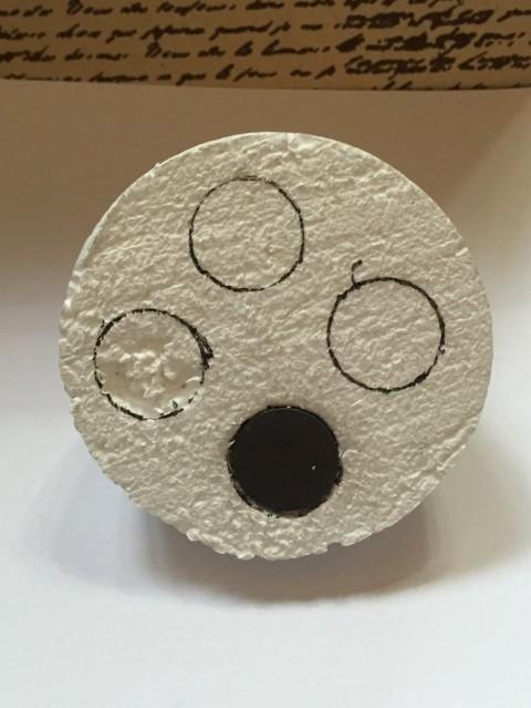 styrofoam ball cut in half, cutting holes to insert weights